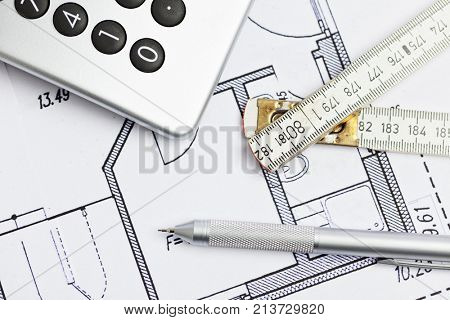 calculator, pencil and yardstick on blueprint of floor plan