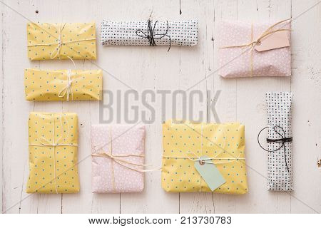 Top view on beautiful gifts wrapped in paper of pastel colors on whote wooden background. Frame made of presents for birthday Christmas or any other celebration.