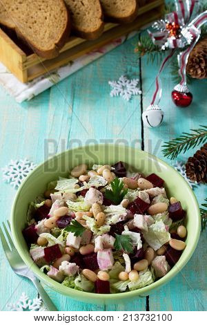Homemade Appetizer On A Festive Christmas Table. Salad With Beets, Peking Cabbage, Meat And Beans.