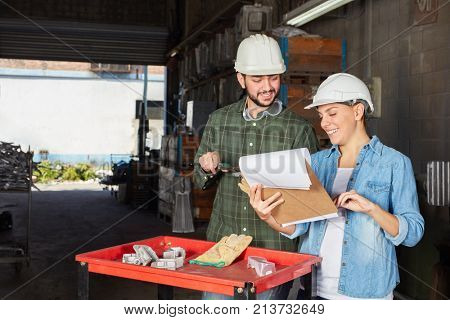 Two metalworkers controlling in teamwork with checklist on clipboard