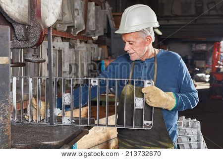 Experienced senior man as worker in foundry holding cast iron