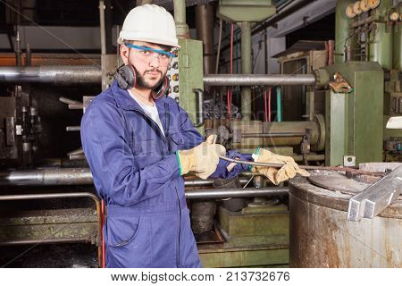 Man as blue collar worker in foundry working and wearing protection