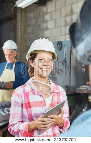 Young woman as metalworker apprentice with laptop in metallurgy factory