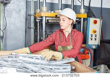 Young woman as blue collar worker apprentice in metallurgy workshop