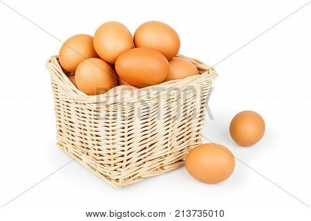 Wicker basket of eggs isolated on white background close-up