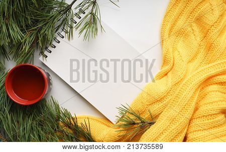 Christmas background with a Cup  of tea, a notebook, branches of pine with large needles and a yellow sweater. Top view, close-up