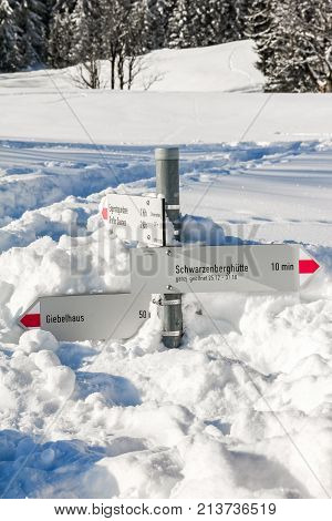 Hiking trail signpost sticks out of deep snow. Mountains winter landscape on sunny day. Allgau, Bavaria, Germany.