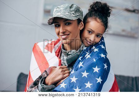african american daughter and female soldier in military uniform wrapped with american flag at home