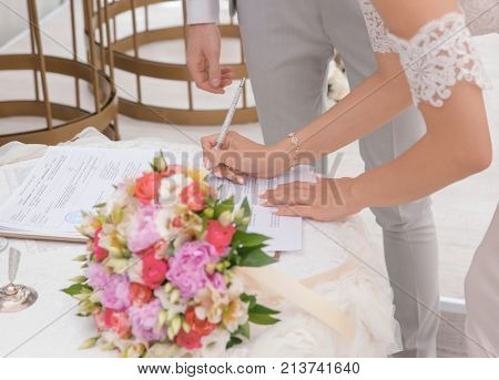 Bride signing marriage certificate, closeup
