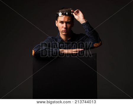 Young wistful man portrait of a confident businessman showing presentation, pointing paper placard black background. Ideal for banners, registration forms, presentation, landings, presenting concept.