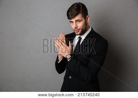 Close-up photo of handsome young man in black suit clap in hands, lookig at camera, isolated over gray background