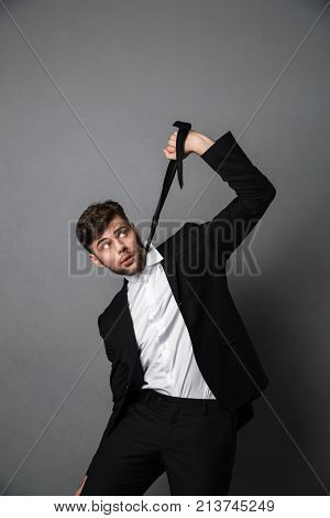 Desperate businessman strangling himself with a tie, isolated over gray background