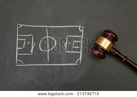 Judge gavel on blackboard background with painted soccer court.