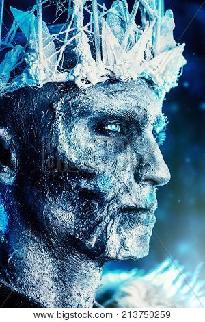 Close-up portrait of The King zombie warrior in the armor of a medieval knight covered with snow. Halloween. Horror fantasy film.