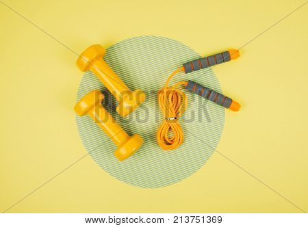 Orange Jump Rope Or Skipping Rope With Dumbbells On Yellow And Green Background.