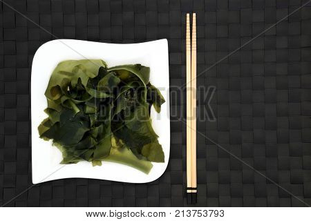 Japanese wakame seaweed food on a square porcelain plate with chopsticks. Has many health benefits and is very high in minerals.