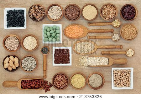 Dried macrobiotic diet health food concept with legumes, seaweed, grain, cereal, nuts, seeds and whole wheat pasta. High in smart carbohydrates, protein, antioxidants and fiber,  top view.