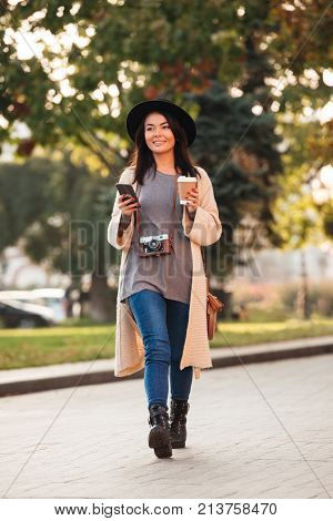 Full lenth photo of pretty modern asian girl holding smartphone and coffee to-go while strolling in public park