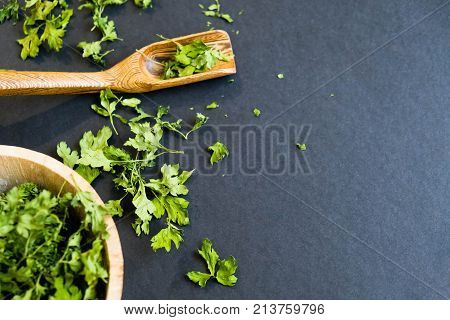 Dried cilantro leaves on a wooden spoon. Natural light. Selective focus. Close up on a black background. Top view, flat lay. copy space. dried grapes.