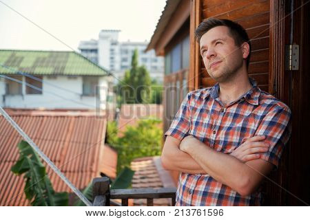 A young man in a checkered shirt is standing on the balcony on a sunny day and with his arms folded on chest he looks dreamily away. He rests while traveling in Thailand, making plans for the future.