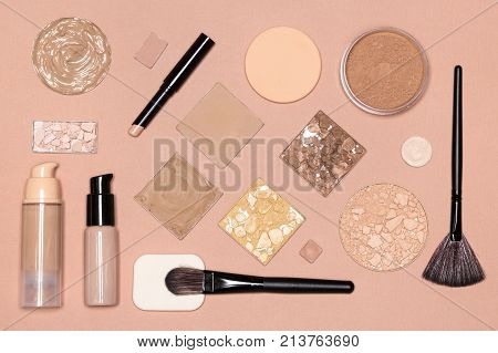 Corrective makeup flat lay set on nude color surface. Concealer pencil, primer, liquid and cream foundation, various functional types of cosmetic powder, make up brushes and sponges