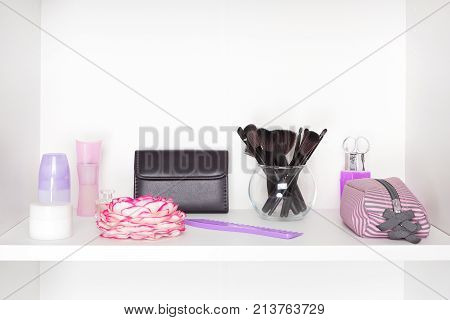 Beauty products and accessories on white shelf inside closet. Cosmetic and makeup storage. Modern woman essentials. Copy space