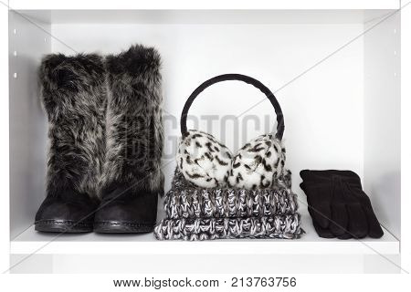 Winter fashion women accessories on white shelf. Faux fur suede boots, knitted scarf, warm earmuffs, black wool gloves