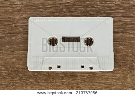 Vintage white audio cassette tape on brown wooden background