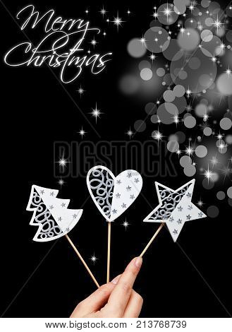 White seasonal christmas decorations in woman hand - copy space on black background