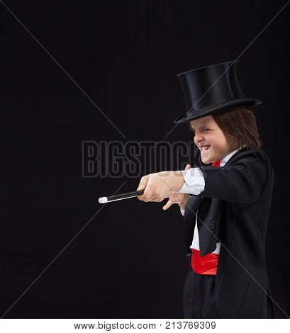 Magician boy with hardhat pointing to copy space with magic wand and making evil grimace with a grin poster