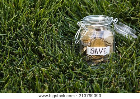 Coins in glass jar on green grass background, copy space. Money box, saving money for dream, pension, vacation. Financial stability concept
