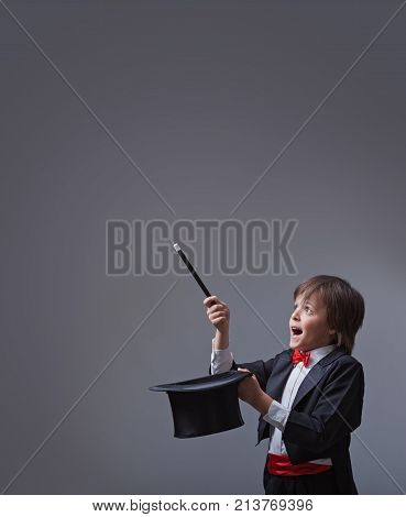 Magician boy performing with magic wand and hard hat - looking up to copy space