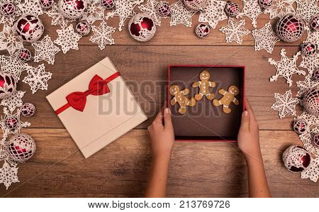 Giving or receiving gingerbread people cookies as christmas present - hands with gift box in seasonal decorations frame