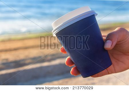 Cup of coffe to go on the sea shore - woman hand closeup with copy space