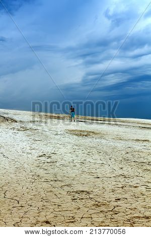 Barren land and stormy skies - woman walking the badlands