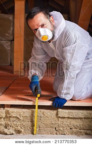 Worker measuring the thickness of heat insulation layer estimating energy efficiency of a house