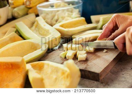 Woman chopping pumpkin slices on cutting board preparing to cook - closeup