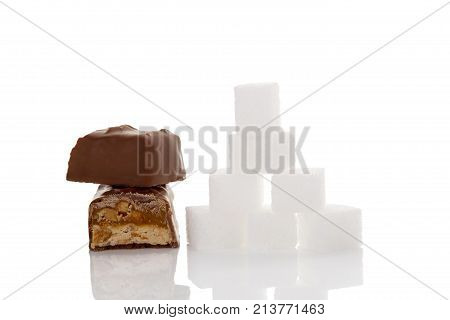 Chocolate bar and sugar cubes isolated on white background. Unhealthy eating. Sugar and carbs.