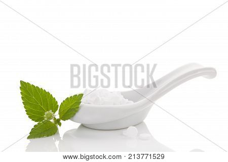 Artificial sweetener pills in white spoon isolated on white background and aztec sweet herb. Natural and artificial sugar. Carbs.