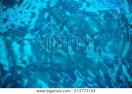 Blue abstract water surface with ripples and waves as background top view