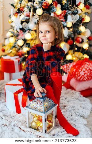 Cute little girl in checkered dress sitiing in brightly decorated room and holding Christmas decoration.