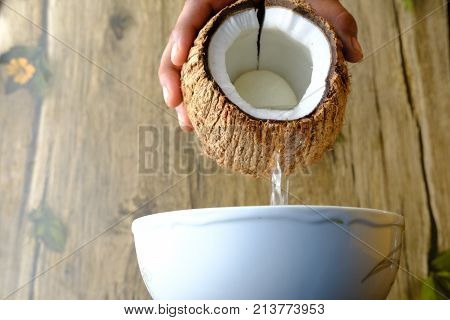 man holding the coconit halves and droping water on bowl.