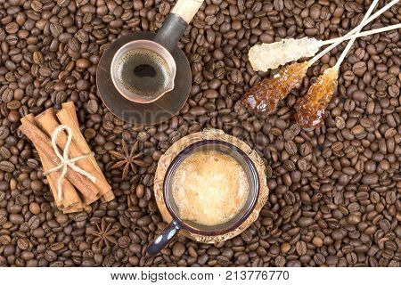 Strong fragrant cooked coffee with foam. A coffee drink in a cup. A cup of coffee sugar stick and coffee pot on coffee beans. Freshly brewed coffee in a pot. Cinnamon near the cup with coffee and cezve top view
