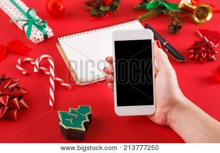 Christmas online shopping. Smartphone and presents list with copy space on red table with christmas staff. Preparing for winter holidays concept