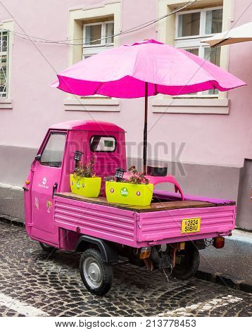 Sibiu Romania October 07 2017 : Pink scooter with closed cockpit and umbrella parked on the Timotei Popovich street in Sibiu city in Romania