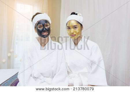Beautiful young Asian women having high quality facial mud mask and high quality and authentic pure gold facial mask waiting for her faces to be cleaned in spa salon