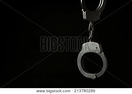 Closed police handcuffs on a black background with text / writing space.