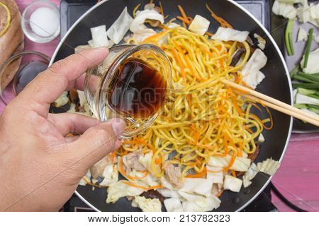 Chef pouring soy sauce for cooking Yakisoba noodle / cooking Yakisoba (Fried Japanese noodle) concept