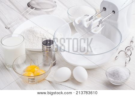 preparation of a protein cream on a white wooden table. Fresh pastry biscuits