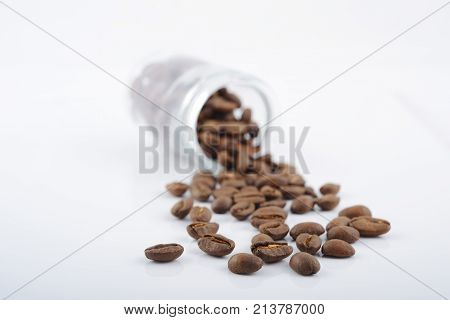 roasted coffee beans poured from clear glass on white background closeup